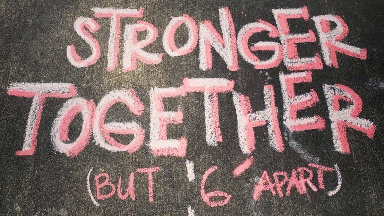 chalk writing on sidewalk - stronger together but six feet apart